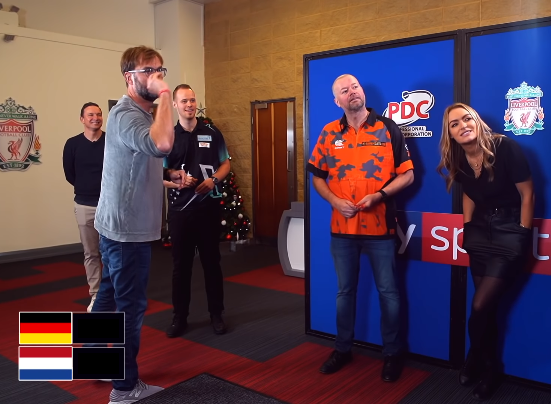 Liverpool Manager Jürgen Klopp Plays Darts Against Raymond van Barneveld